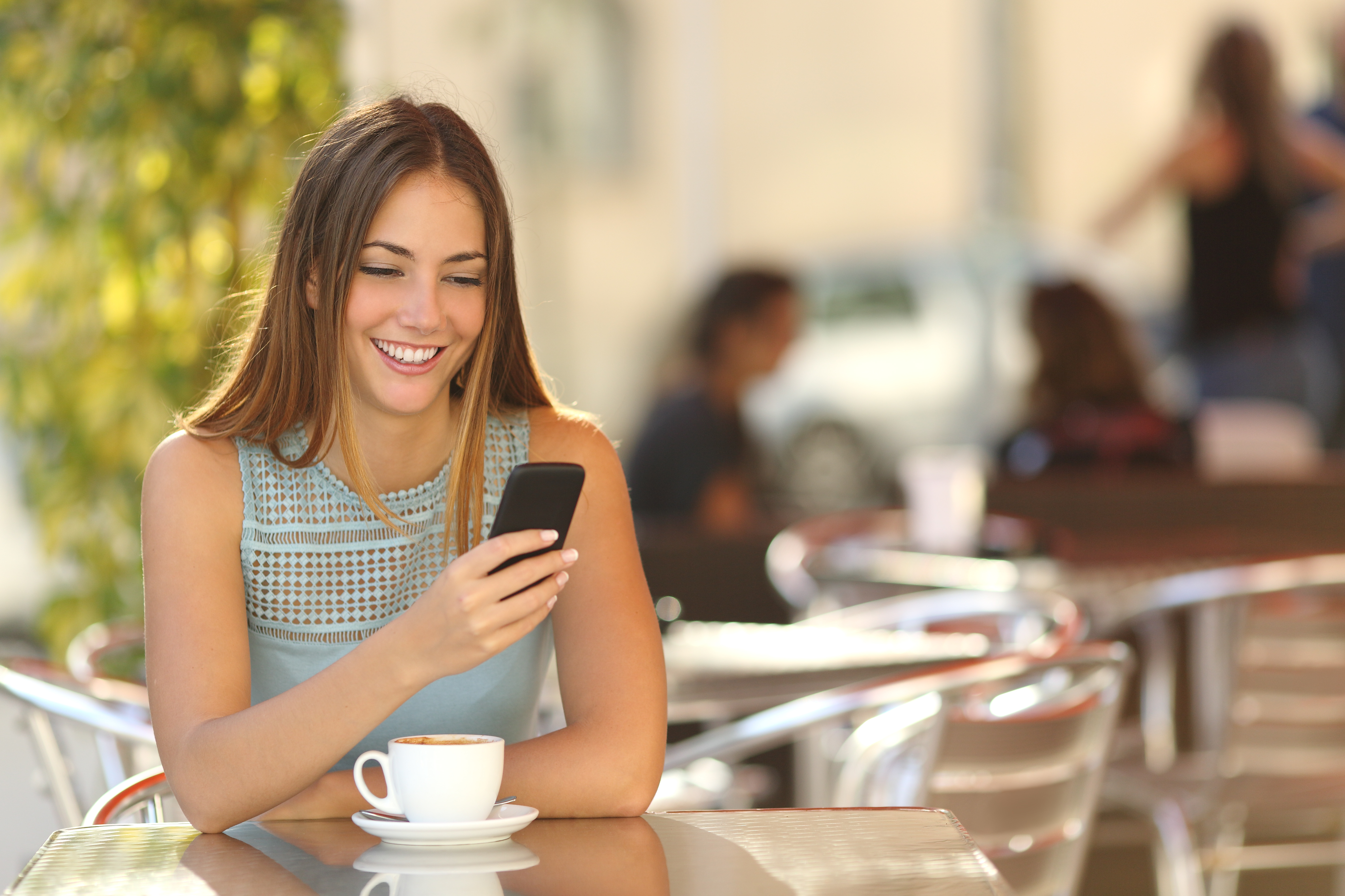 girl on cell phone at cafe looking at high SEO content
