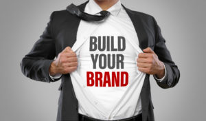 """A man wearing a shirt that says """"Build Your Brand"""""""