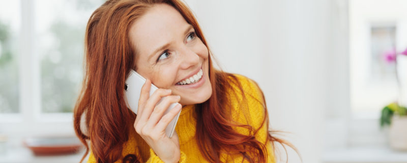 A red-haired woman smiles as she talks on her cell phone