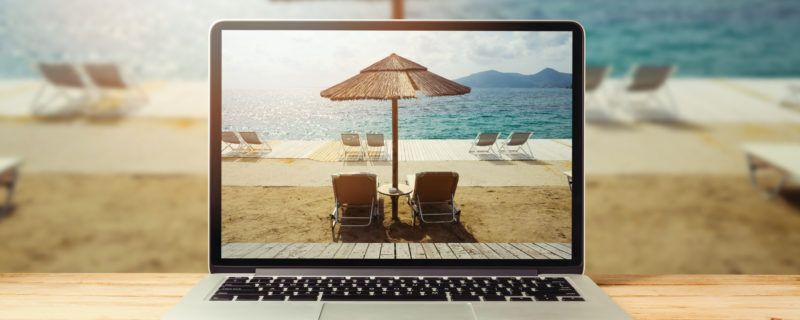 Laptop computer with sunny beach image on wooden table. Summer vacation photo sharing