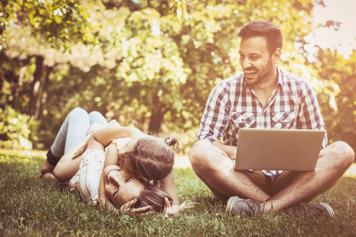 Father with laptop smiles as his family plays in park