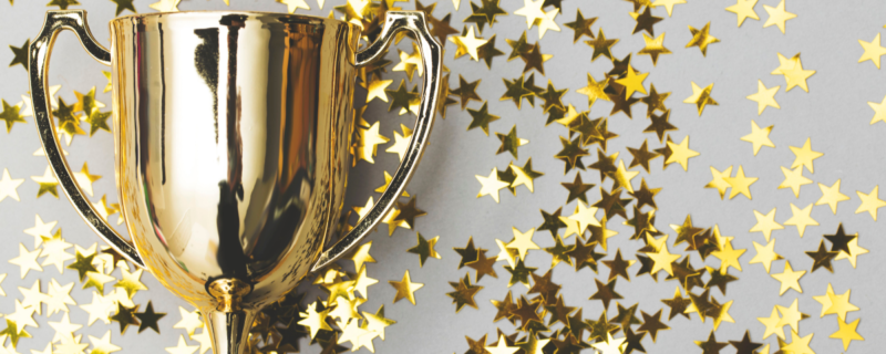 gold trophy with gold star confetti